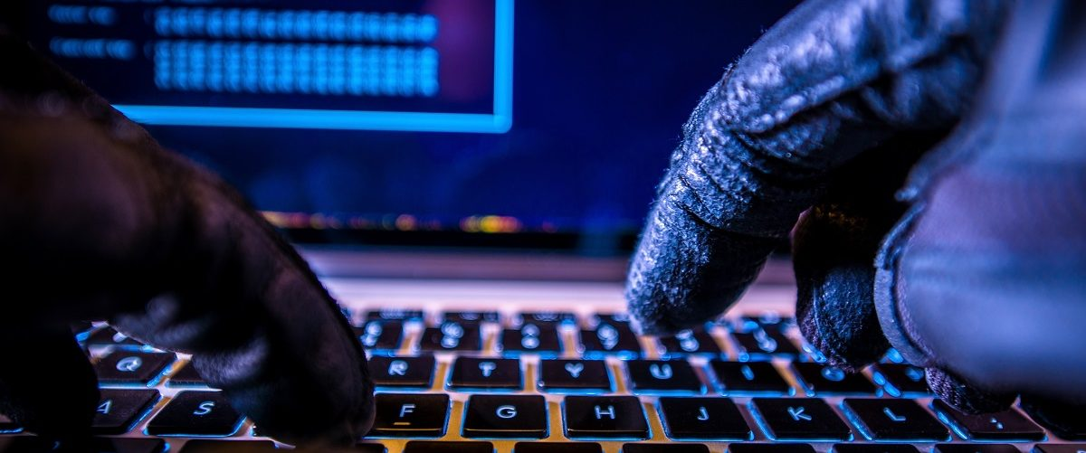 Hacker in black gloves hacking. Welcomia/Shutterstock.