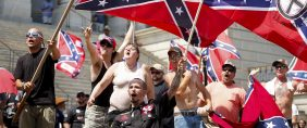 Members of the Ku Klux Klan yell as they fly Confederate flags during a rally at the statehouse in Columbia, South Carolina July 18, 2015. A Ku Klux Klan chapter and an African-American group planned overlapping demonstrations on Saturday outside the South Carolina State House, where state officials removed the Confederate battle flag last week. REUTERS/Chris Keane.