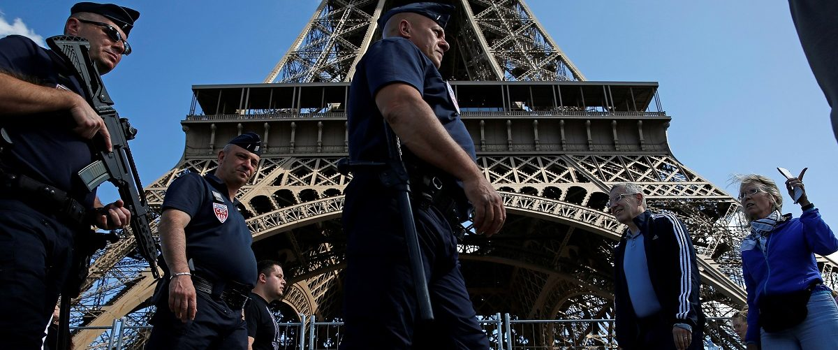 French CRS policemen patrol as tourists walk past in front of the Eiffel Tower in Paris