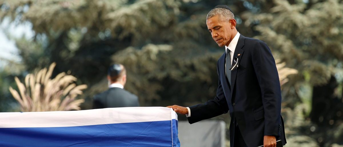 U.S. President Barack Obama touches the casket of former Israeli President Shimon Peres after speaking at his funeral at the Mount Herzl cemetery in Jerusalem, September 30, 2016.   REUTERS/Kevin Lamarque