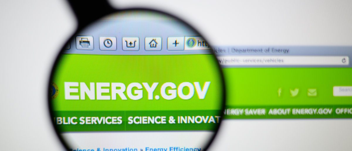 Photo of the United States Department of Energy (DOE) homepage on a monitor screen through a magnifying glass. (Shutterstock/Gil C)