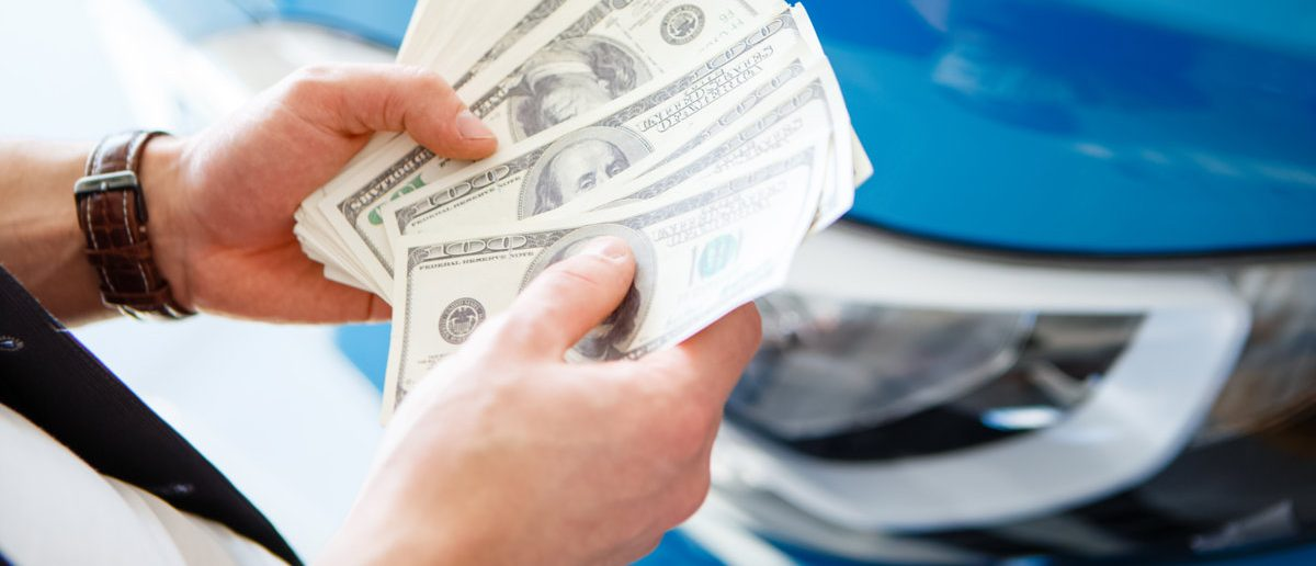 Cash in hand above a new car. (Shutterstock/Roman Seliutin)