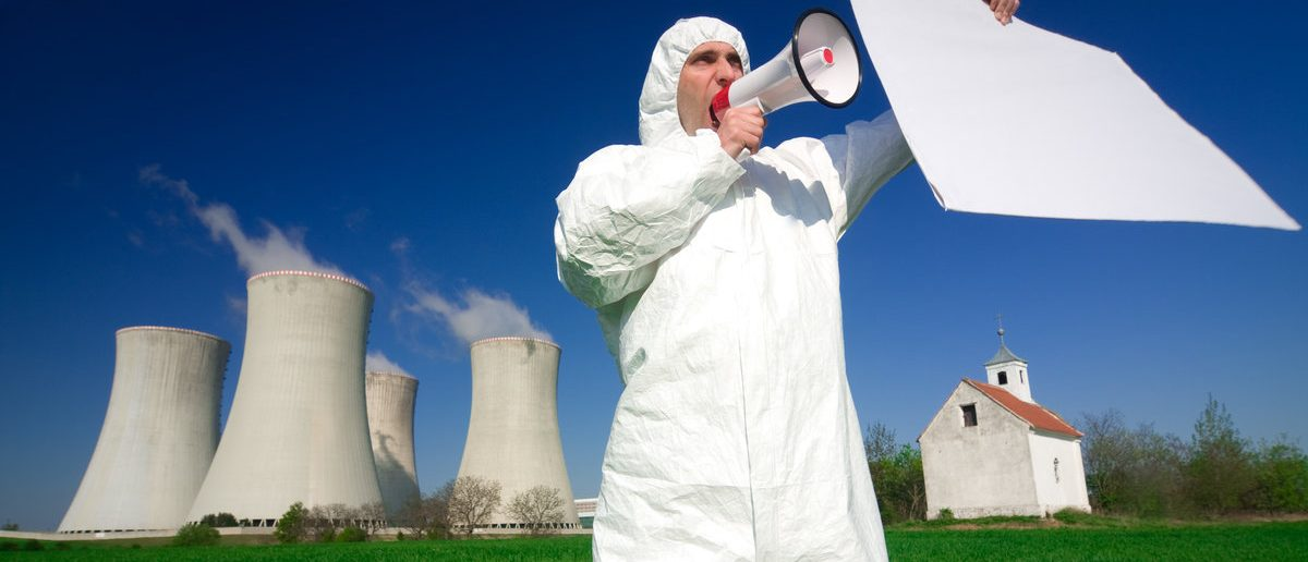 A environmental activist protesting with a blank banner in front of nuclear power plant.(Shutterstock/Rene Jansa)