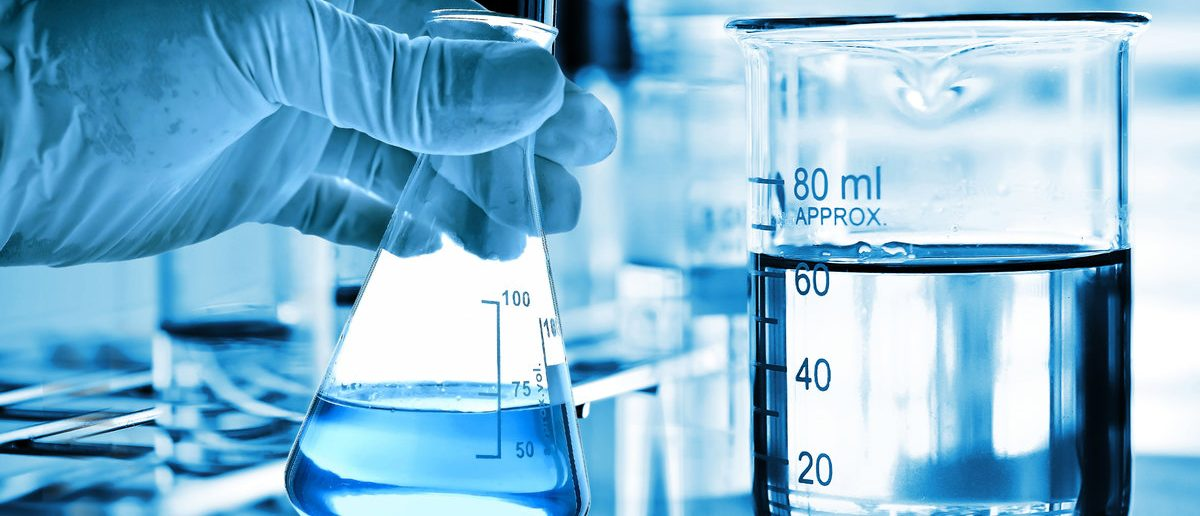 Flask in scientist hand with glassware in laboratory near water (Shutterstock/totojang1977)