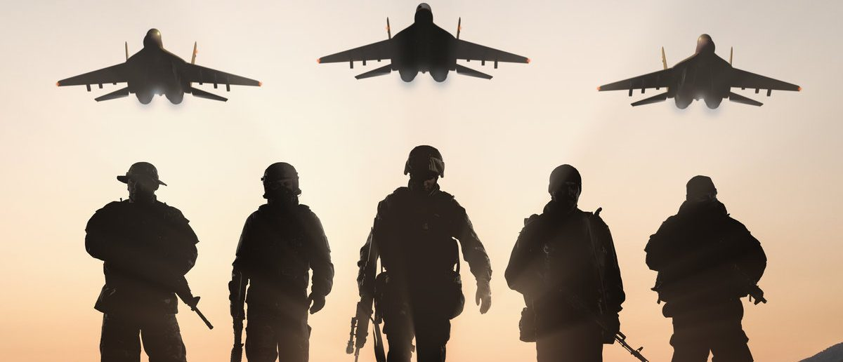Military silhouettes of soldiers and airforce against the backdrop of sunset sky. (Shutterstock/BPTU)