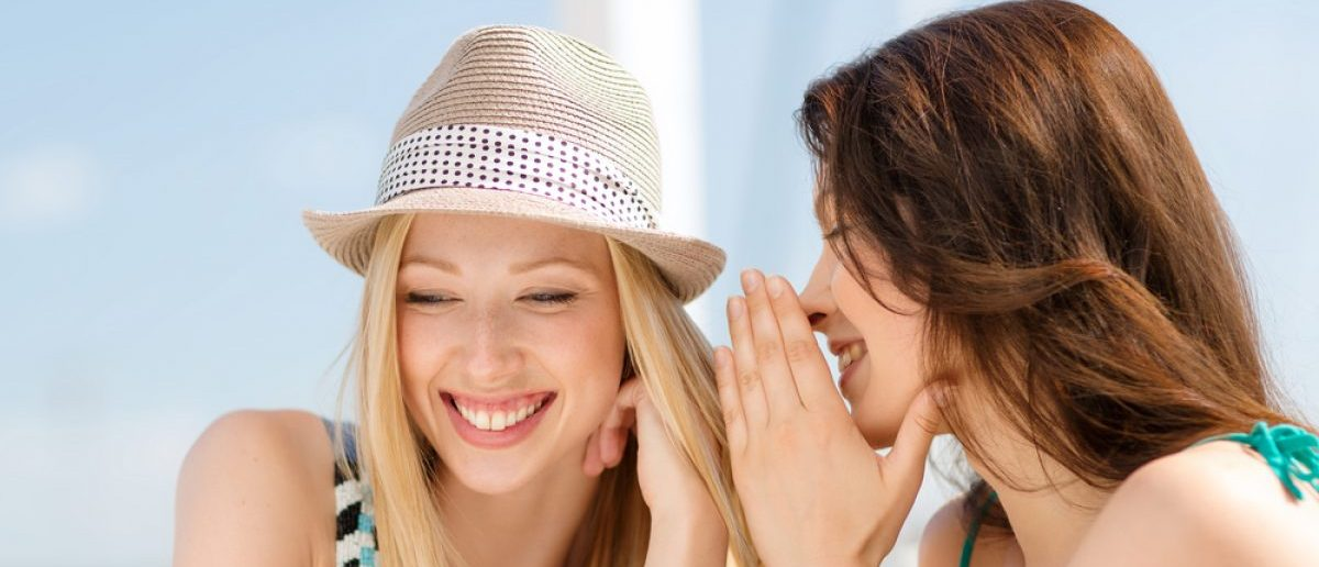 Two girls gossiping in cafe on the beach while traveling. [Shutterstock - Syda Productions - 171690821]