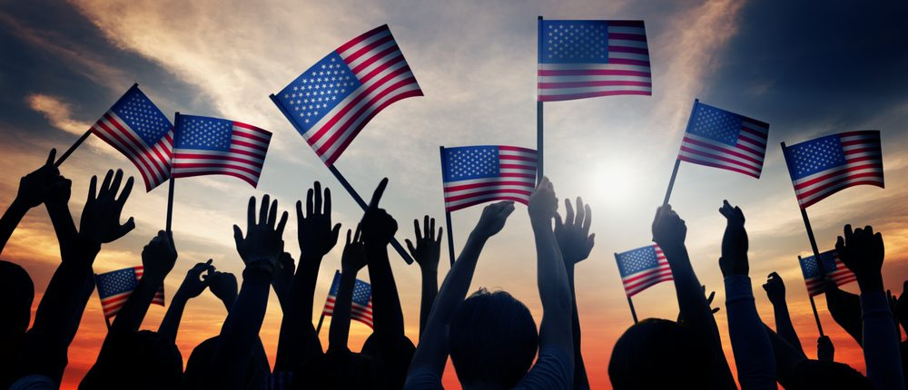 People hold American flags (Shutterstock)