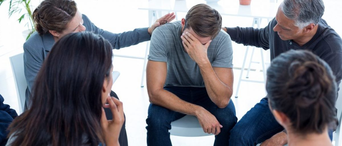 Concerned patients comforting another in rehab group at a therapy session. (Credit: wavebreakmedia / shutterstock.com)