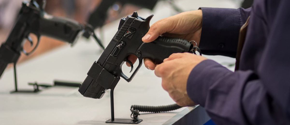 Man examines a gun during an exhibition. Source: Shutterstock/DmyTo