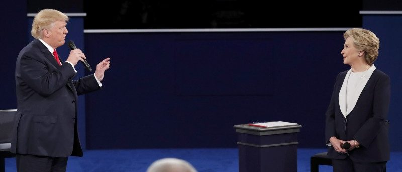 Republican U.S. presidential nominee Donald Trump speaks as Democratic U.S. presidential nominee Hillary Clinton looks on during their second presidential debate at Washington University in St. Louis