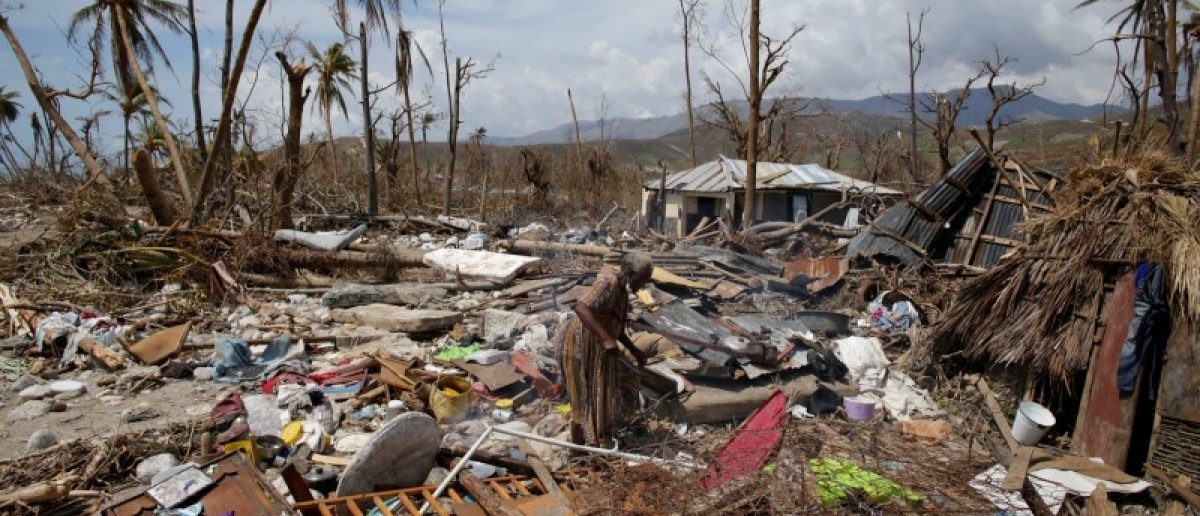A woman walks on debris in an area devastated by Hurricane Matthew in Port-a-Piment, Haiti, October 9, 2016.
