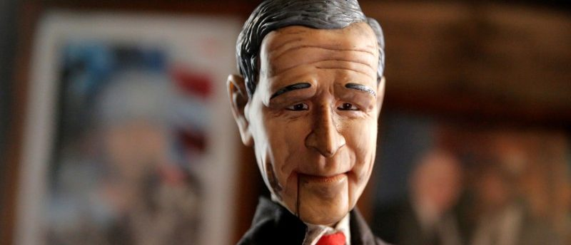 A doll featuring the likeness of George W. Bush is seen in the damage caused in a firebomb attack on local offices of the North Carolina Republican Party in Hillsborough