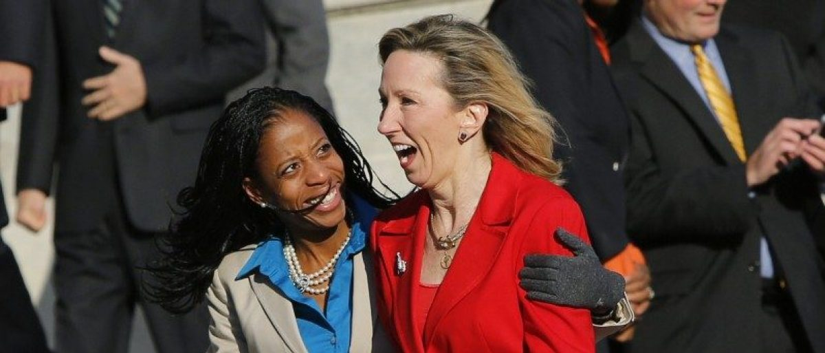 Freshman members of the incoming U.S. 114th Congress Mia Love (R-UT) (L) and Barbara Comstock (R-VA) huddle together in freezing temperatures after participating in a class photo on the steps of the U.S. Capitol in Washington in a November 18, 2014 file photo.  REUTERS/Gary Cameron