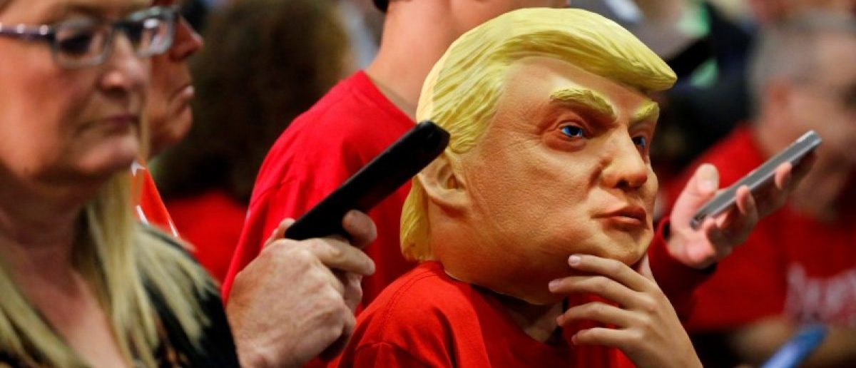 A boy wears a Trump mask as supporters rally with Republican U.S. presidential nominee Donald Trump in Fletcher, North Carolina, U.S. October 21, 2016. REUTERS/Jonathan Ernst
