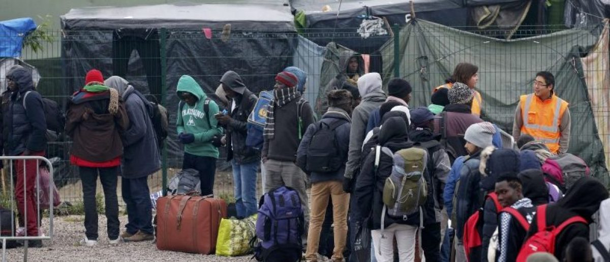 """Migrants with their belongings queue at the start of their evacuation and transfer to reception centers in France, and the dismantlement of the camp called the """"Jungle"""" in Calais, France, October 24, 2016. REUTERS/Pascal Rossignol"""