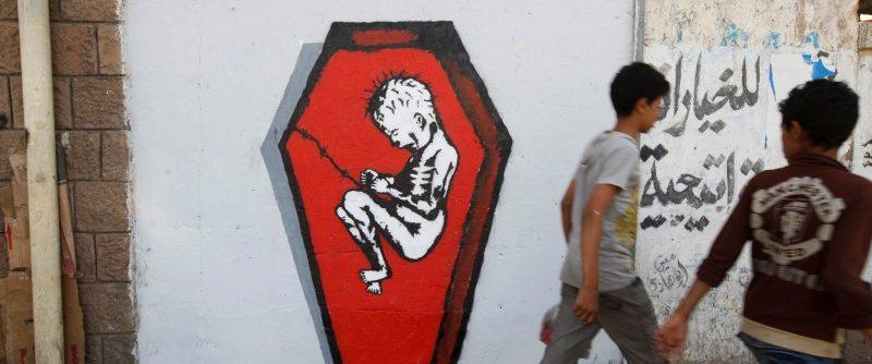 Boys walks pass a graffiti of artist Murad Subai depicting a child suffering from malnutrition in a coffin along a street in Sanaa, Yemen