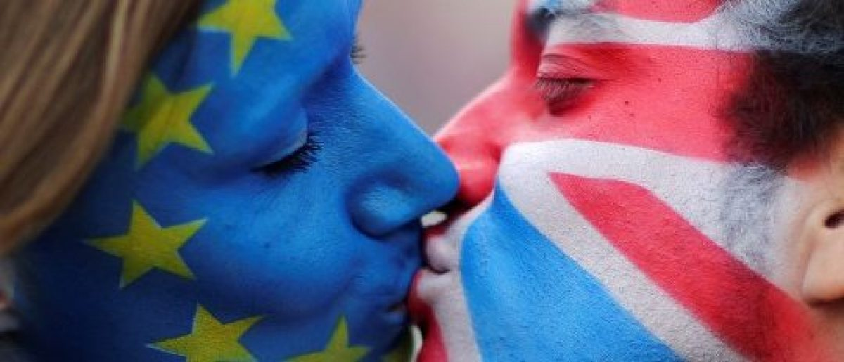 Two activists with the EU flag and Union Jack painted on their faces kiss each other in front of Brandenburg Gate to protest against the British exit from the European Union, in Berlin, Germany, June 19, 2016. REUTERS/Hannibal Hanschke/File Photo