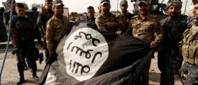 Iraqi soldiers pose with the Islamic State flag along a street of the town of al-Shura, which was recaptured from Islamic State (IS) on Saturday, south of Mosul, Iraq October 30, 2016. REUTERS/Zohra Bensemra