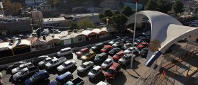 """NOGALES, AZ - DECEMBER 10: Hundreds of cars wait to pass from Mexico into the United States at the border crossing on December 10, 2010 in Nogales, Arizona. Despite Arizona's tough immigration enforcement laws, thousands of Mexican citizens have permits to work in the U.S. and commute daily from their homes across the border in Mexico. Border crossings, known as """"ports of entry,"""" are run by the U.S. Office of Field Operations, which is part of the department of U.S. Customs and Border Protection. Port personnel are the face at the border for most visitors and cargo entering the United States and are authorized to stop, question, search and examine everyone entering the country. (Photo by John Moore/Getty Images)"""