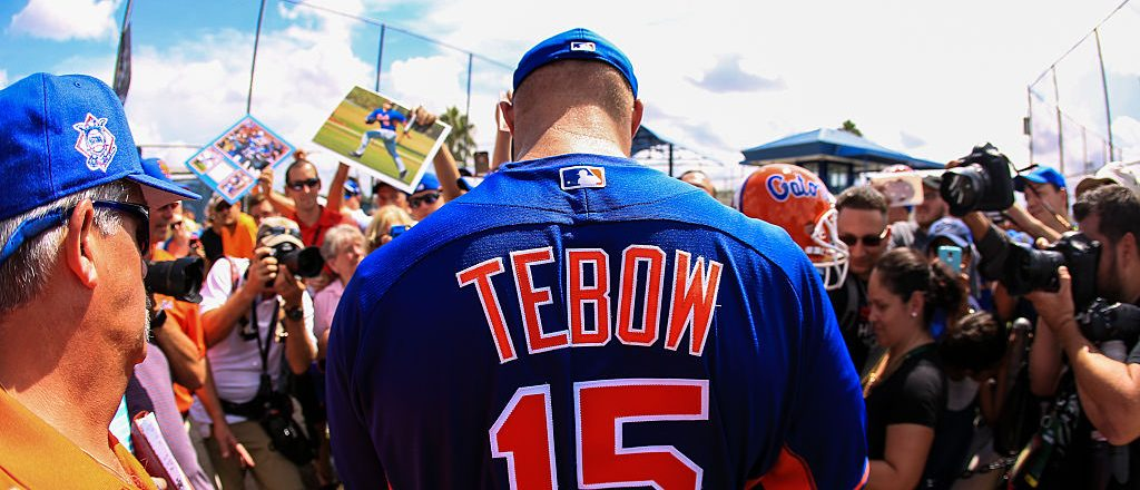 Tim Tebow signs autographs for fans. (Photo credit: Getty Images)