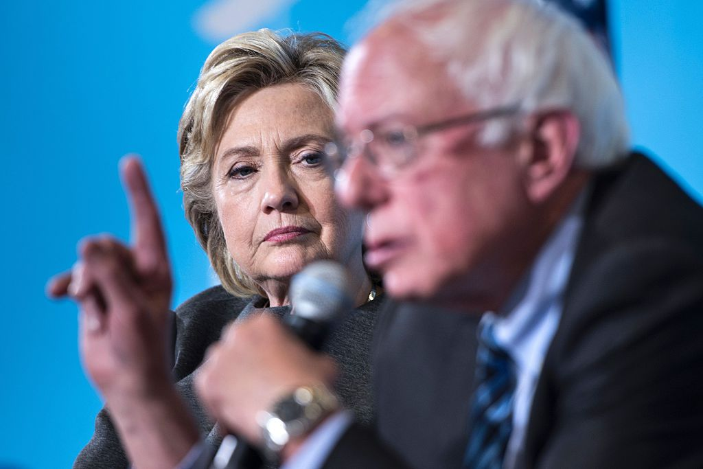 Hillary Clinton listens as Bernie Sanders speaks during an event at the University of New Hampshire on September 28, 2016 (Getty Images)