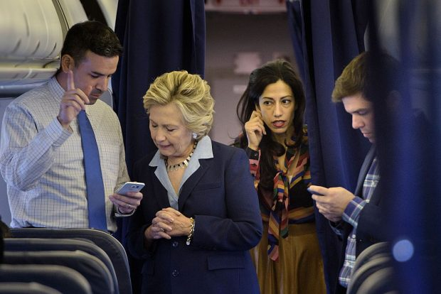 Hillary Clinton looks at national press secretary Brian Fallon's smart phone while on her plane with aid Huma Abedin and traveling press secretary Nick Merrill Getty Images)