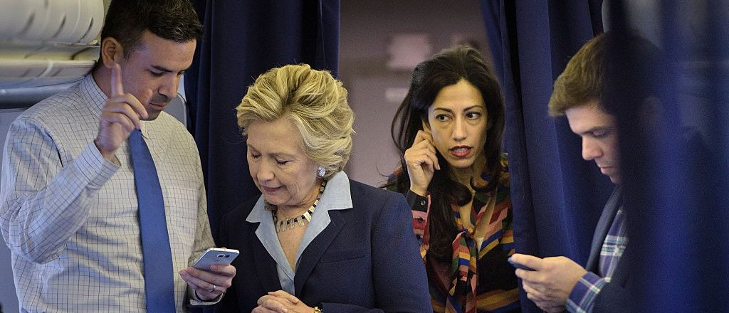 Democratic presidential nominee Hillary Clinton (2L) looks at national press secretary Brian Fallon's (L) smart phone while on her plane with aid Huma Abedin (2R) and traveling press secretary Nick Merrill (R) at Westchester County Airport October 3, 2016 in White Plains, New York. / AFP / Brendan Smialowski (Photo credit should read BRENDAN SMIALOWSKI/AFP/Getty Images)