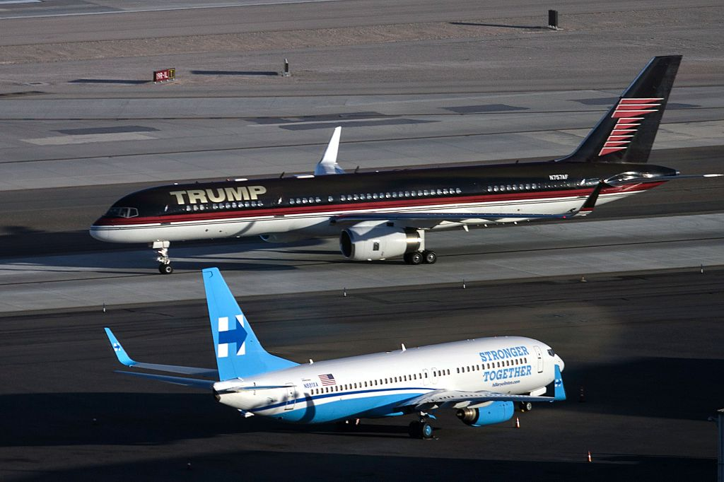 Republican presidential nominee Donald Trump's plane (TOP) passes Democratic presidential nominee Hillary Clinton's campaign plane on the tarmac in Las Vegas, Nevada before the third and final US presidential debate. (Photo credit should read BRENDAN SMIALOWSKI/AFP/Getty Images)