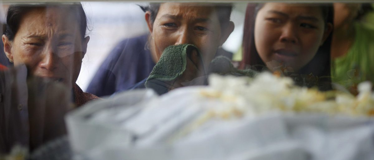 Family members cry behind the body of their relative at Yaeway cemetery in Yangon, during a ceremony provided by Yangon's Free Funeral Services Society, June 26, 2011. REUTERS/Soe Zeya Tun