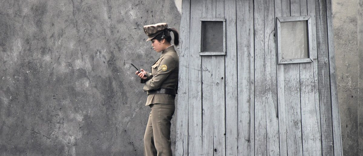 A female North Korean soldier uses her mobile phone next to a sentry on the banks of the Yalu River, near the North Korean town of Sinuiju, opposite the Chinese border city of Dandong June 1, 2014. REUTERS/Jacky Chen