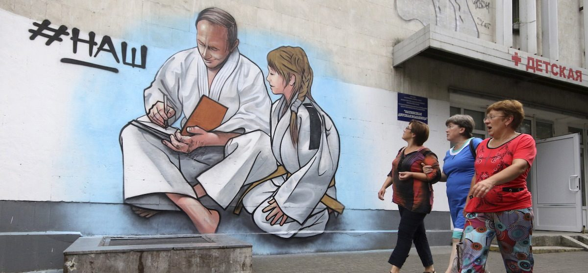 """Women walk past graffiti depicting Russian President Vladimir Putin, dressed in a Judogi and sitting next to a girl, on the facade of a children's health centre in Yalta, Crimea, August 19, 2015. The painted word reads """"Ours"""". REUTERS/Pavel Rebrov - RTX1OTQ7"""
