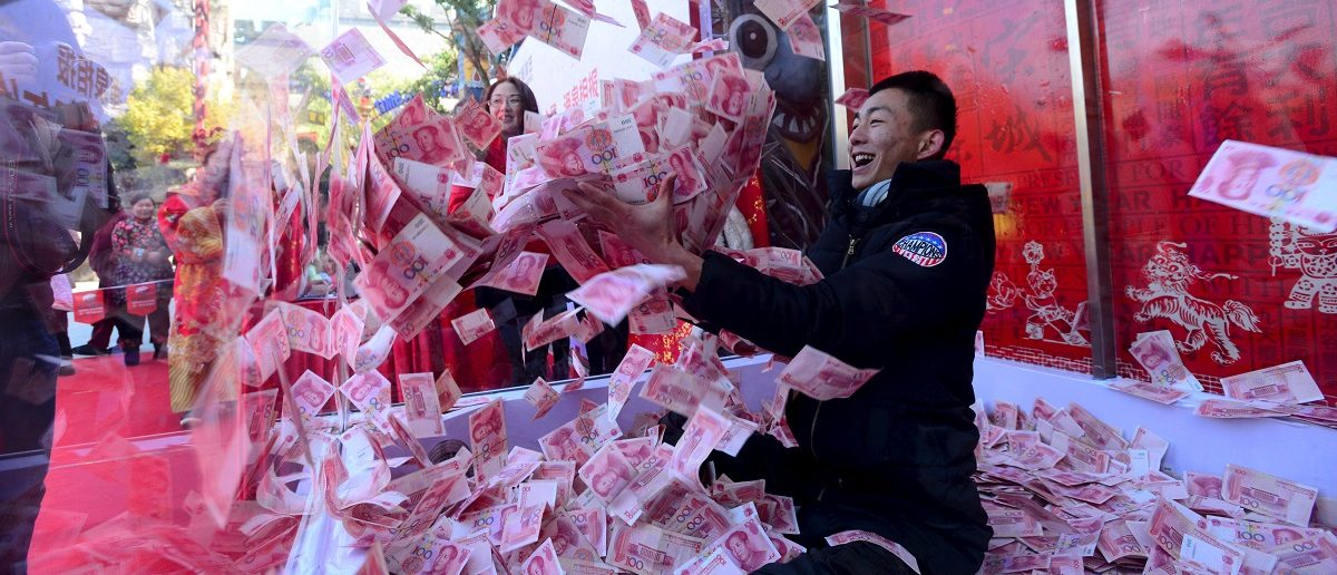 A man tries to snatch 100-yuan banknotes inside a glass cage during an event held to celebrate the upcoming Spring Festival, at a park in Hangzhou, Zhejiang province, China January 26, 2016. The event offered 5 million yuan ($760,000) for 10 visitors to snatch inside a glass cage with an air blower on. The visitors were allowed to take away all the money they could grab with their hands within one minute. One of the visitors won 18,300 yuan ($2,800) from the game, according to local media.  REUTERS/Stringer