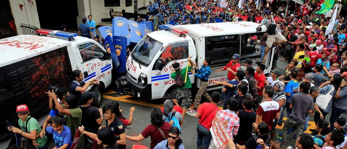 Protesters try to trash a police mobile patrol vehicle as they join various activist and Indigenous People's (IP) groups in a protest against the continuing presence of U.S. troops in the Philippines in front of the U.S. Embassy in metro Manila, Philippines October 19, 2016. REUTERS/Romeo Ranoco