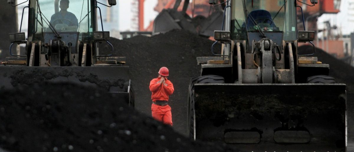 An employee walks between front-end loaders which are used to move coal imported from North Korea at Dandong port in the Chinese border city of Dandong, Liaoning province December 7, 2010. REUTERS/Stringer/File Photo