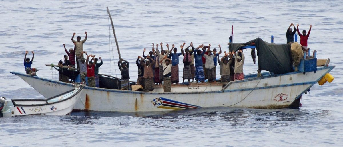 """Hostages and pirates stand with their hands up before the intervention of Dutch NATO soldiers off Somalia's coast in this NATO handout photo made available April 18, 2009. Dutch commandos freed 20 Yemeni hostages on Saturday and briefly detained seven pirates who had forced the Yemenis to sail a """"mother ship"""" attacking vessels in the Gulf of Aden, NATO officials said. REUTERS/NATO/Handout"""