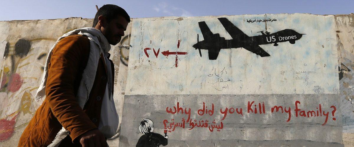 Man walks past a graffiti, denouncing strikes by U.S. drones in Yemen, painted on a wall in Sanaa