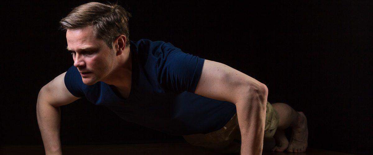 Man doing pushups on floor. (levelupart/Shutterstock.)