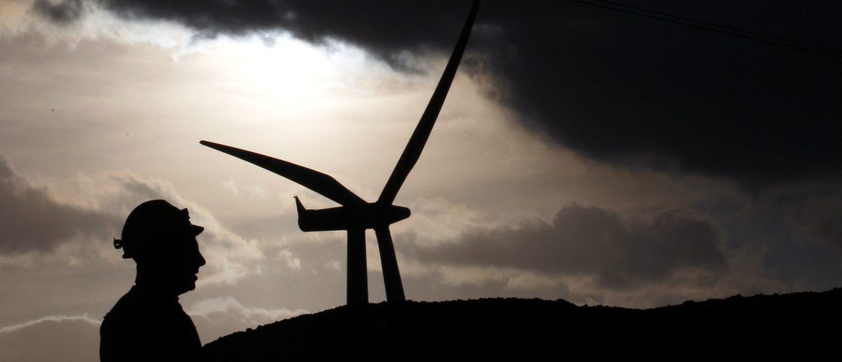 An Alcoa Inc. aluminium worker is silhouetted next to Aeolian Power's wind turbine in Sardinian, in Portovesme, next to Cagliari, Italy, September 1, 2012. (REUTERS/Alessandro Bianchi/ File Photo)