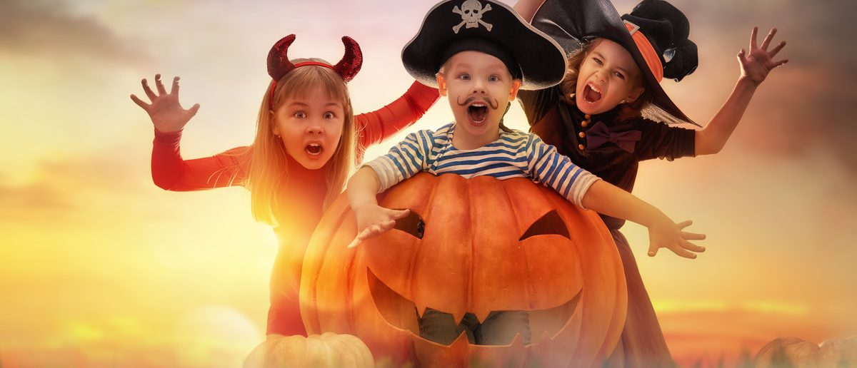 Happy brother and two sisters on Halloween. Funny kids in carnival costumes outdoors. Cheerful children and pumpkins on sunset background. (Shutterstock/Yuganov Konstantin)