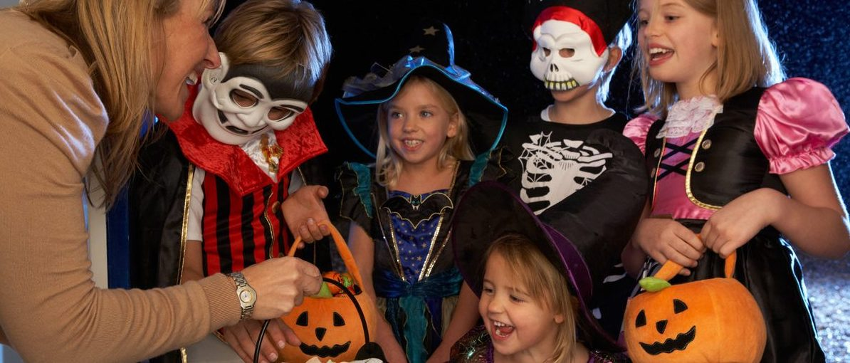 Happy Halloween party with children trick or treating (Shutterstock/Monkey Business Images)
