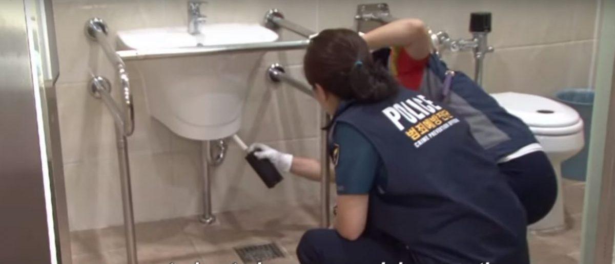 South Korean police scan restroom for hidden cameras (Youtube screenshot)