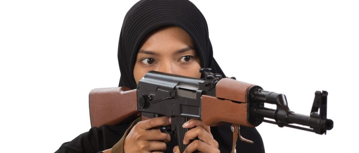 Woman with a machine gun isolated on white background. Muslim woman pointing a machine gun. An armed woman shoots a machine gun on a white background. Woman holding an automatic weapon. (Credit: Milkovasa / shutterstock.com)