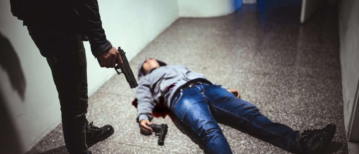 Hitman with dead victim. [Shutterstock - Dragon Images]