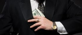 Businessman with money in studio. Currency bribing. Businessman hiding money in jacket pocket. Corruption and fraud concepts. (lipik/Shutterstock)