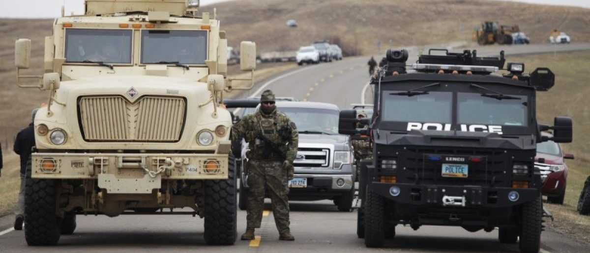 A North Dakota law enforcement officers stands next to two armored vehicles just beyond the police barricade on Highway 1806 near a Dakota Access Pipeline construction site. REUTERS/Josh Morgan