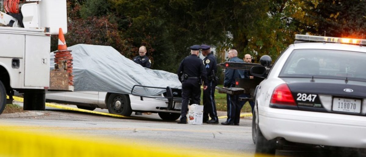 """Police officers cover a squad car at the scene of a police shooting in Des Moines, Iowa, where one of two police officers were shot and killed in separate attacks described as """"ambush-style"""" in Urbandale and Des Moines, Iowa, U.S., November 2, 2016. REUTERS/Scott Morgan"""