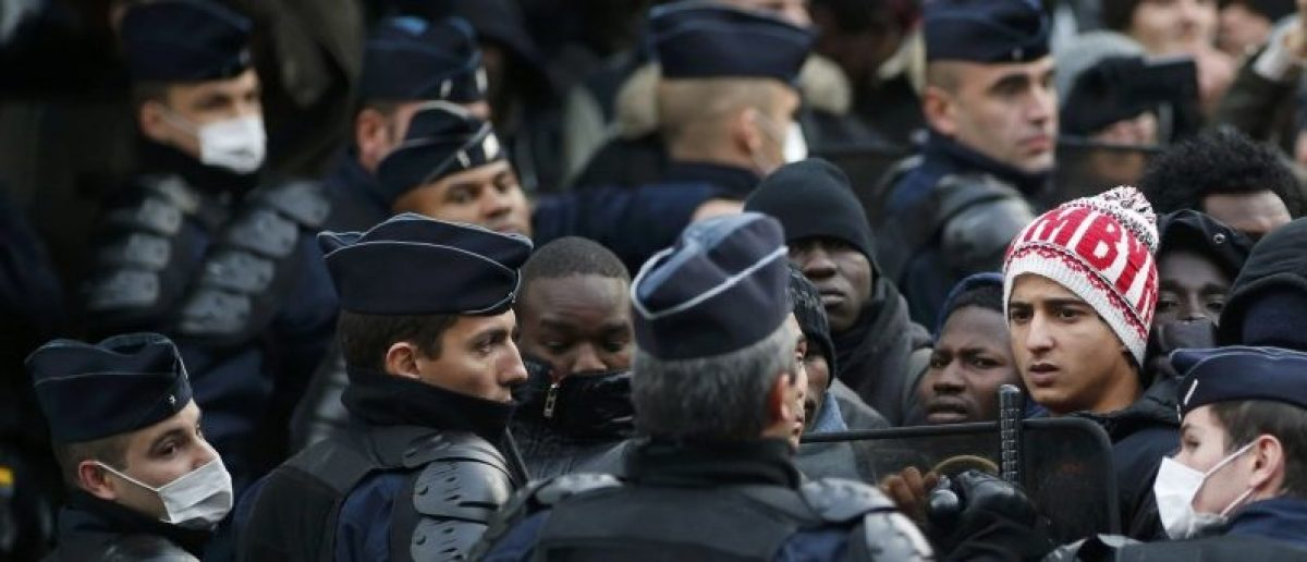 French riot police officers secure the area as migrants wait before entering buses as part of their transfer by French authorities to reception centres across the country during the dismantlement of makeshift camps in a street near Stalingrad metro station in Paris, France, November 4, 2016. REUTERS/Benoit Tessier
