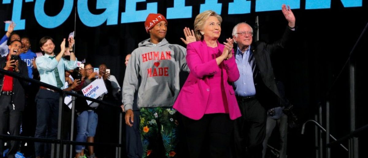Hillary Clinton takes the stage with musician Pharrell Williams and Senator Bernie Sanders at a campaign rally in Raleigh, North Carolina. REUTERS/Brian Snyder