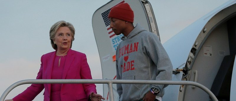 Hillary Clinton is joined by musician Pharrell Williams at her campaign plane in Morrisville, North Carolina. REUTERS/Brian Snyder