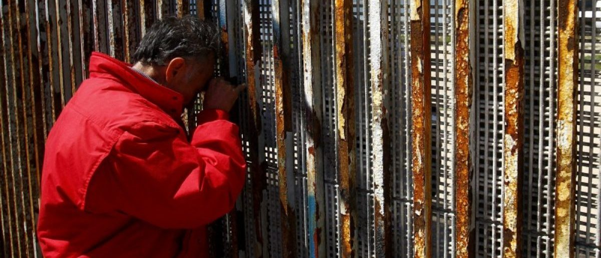 A man talks to relatives at a wall separating Mexico and the United States, as photographed from Playas Tijuana, in Tijuana, Mexico, April 10, 2016. REUTERS/Jorge Duenes/File Photo